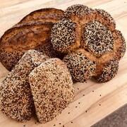 Des pains couverts de grains de différentes formes sur une table