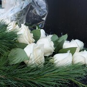 Une gerbe de roses blanches et de feuillage de pin.