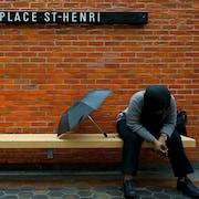Une femme assise sur un banc à la station de métro Place-St-Henri