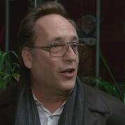 Un homme parle avec en arrière-plan des plantes vertes.