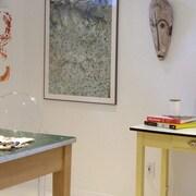 studio d'artiste avec chat sur table, tableaux, masque africain et toiles