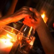 Un couple se tient la main lors d'un souper aux chandelles.