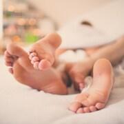Un plan rapproché des pieds d'un homme et d'une femme entremêlés dans un lit.