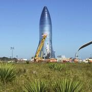 Une fusée métallique autour de laquelle une grue s'élève.