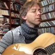 Fred Pellerin joue de la guitare dans sa bibliothèque.