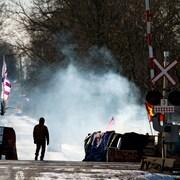 Une personne se trouve près d'une voie ferrée. Des drapeaux et des pancartes se trouvent près des rails.