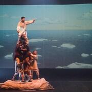 Des artistes forment une pyramide humaine sur scène.