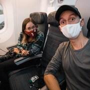 MJ Lalande et Alex Normand dans un avion. Tous deux portent des masques.