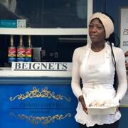 Nia Bangala, pose devant son commerce avec une boîte de beignets.