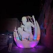Sculpture géante éclairée d'une figure qui semble sortir d'un oeuf,