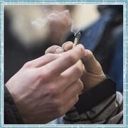En gros plan, une main qui donne une cigarette de cannabis à une autre main.