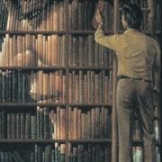 Un homme prend un livre dans une bibliothèque.