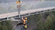 Un ingénieur est accroché dans le vide sur un pont suspendu. Son collègue est sur le pont.