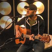 Un homme jouant de la guitare chante dans un micro.
