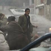 Un homme (Niels Schneider) au milieu d'une rue enfumée jonchée de cadavres et de débris.