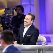L'animateur Guy A. Lepage est assis sur son siège d'intervieweur et regarde ses invités.