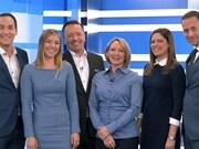 Les membres de l'équipe de l'émission sont côte-à-côte dans le studio et sourient à la caméra.