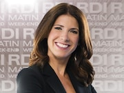 Caroline Lacroix est debout, bras croisés et souriante dans le décor de l'émission.