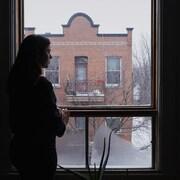 Une jeune dame regarde par la fenêtre de son appartement.