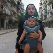 Une femme portant un bébé dans une rue dévastée.