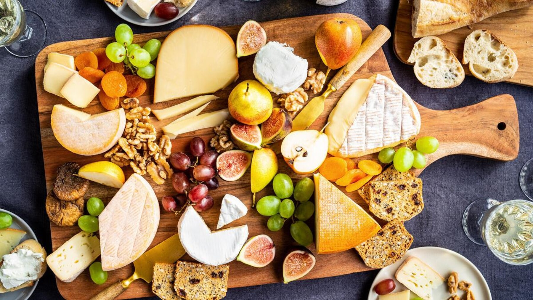 Plateau de plusieurs fromages fins avec des noix, des fruits et des craquelins.