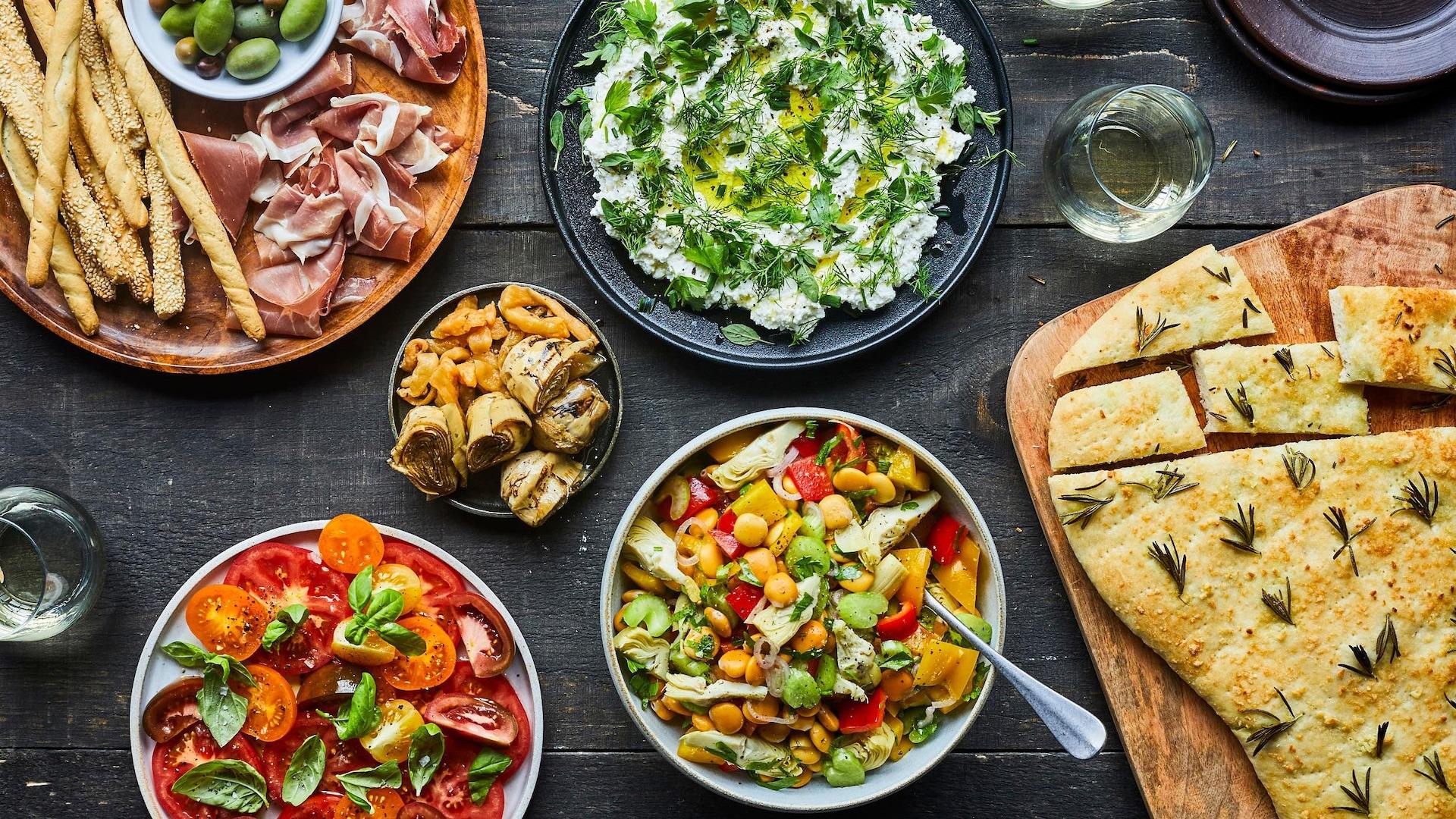 Sur une table est disposée une salade tomate avec des  feuilles de basilic, des cœurs de palmier, une fougasse au romarin, des tranches de prosciutto.