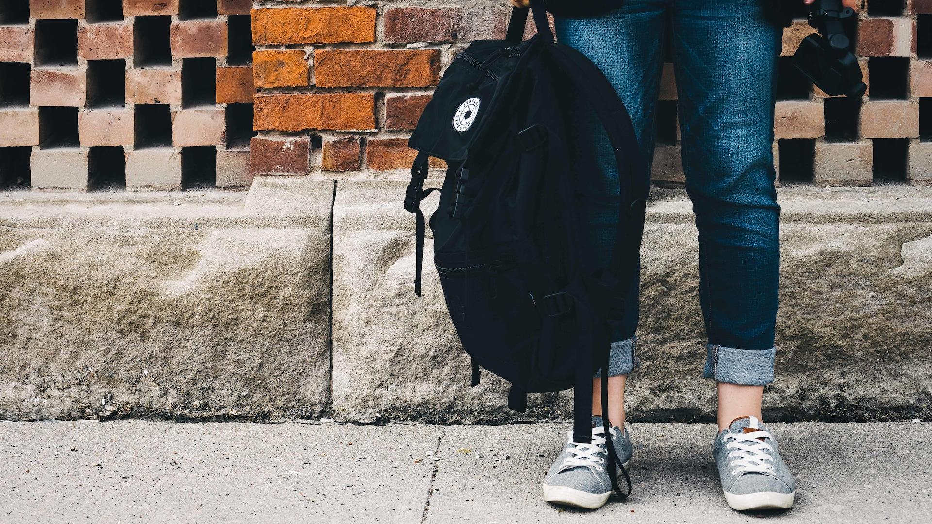 Une personne tient à la main la ganse du haut de son sac à dos.