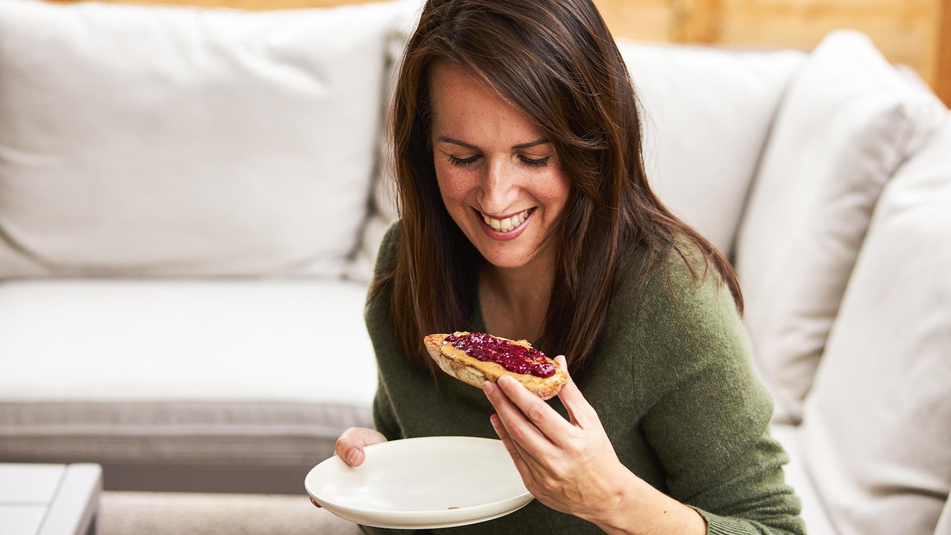 Geneviève O'Gleman qui s'apprête à manger une tranche de pain garnie de beurre d'arachide et de confiture.