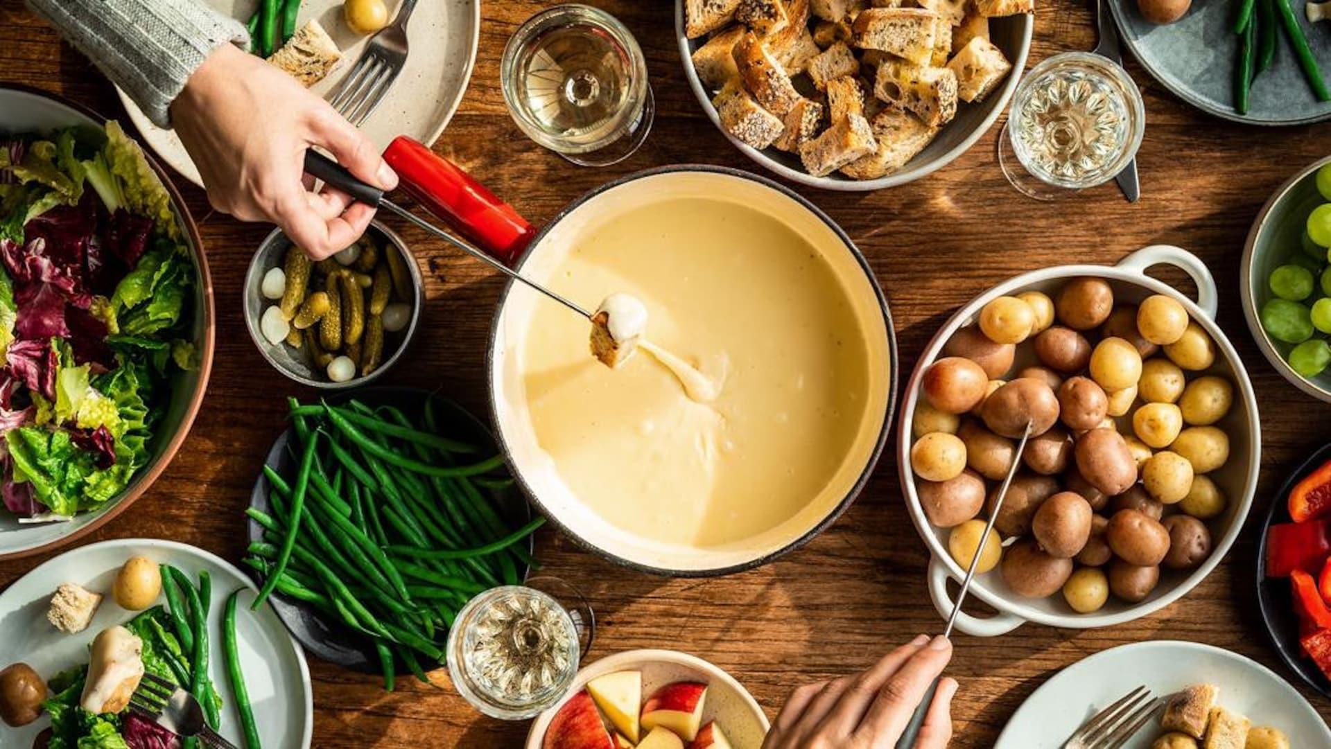 Fondue au fromage entourée de morceaux de pain, de pommes de terre grelot, de fruits et de légumes.