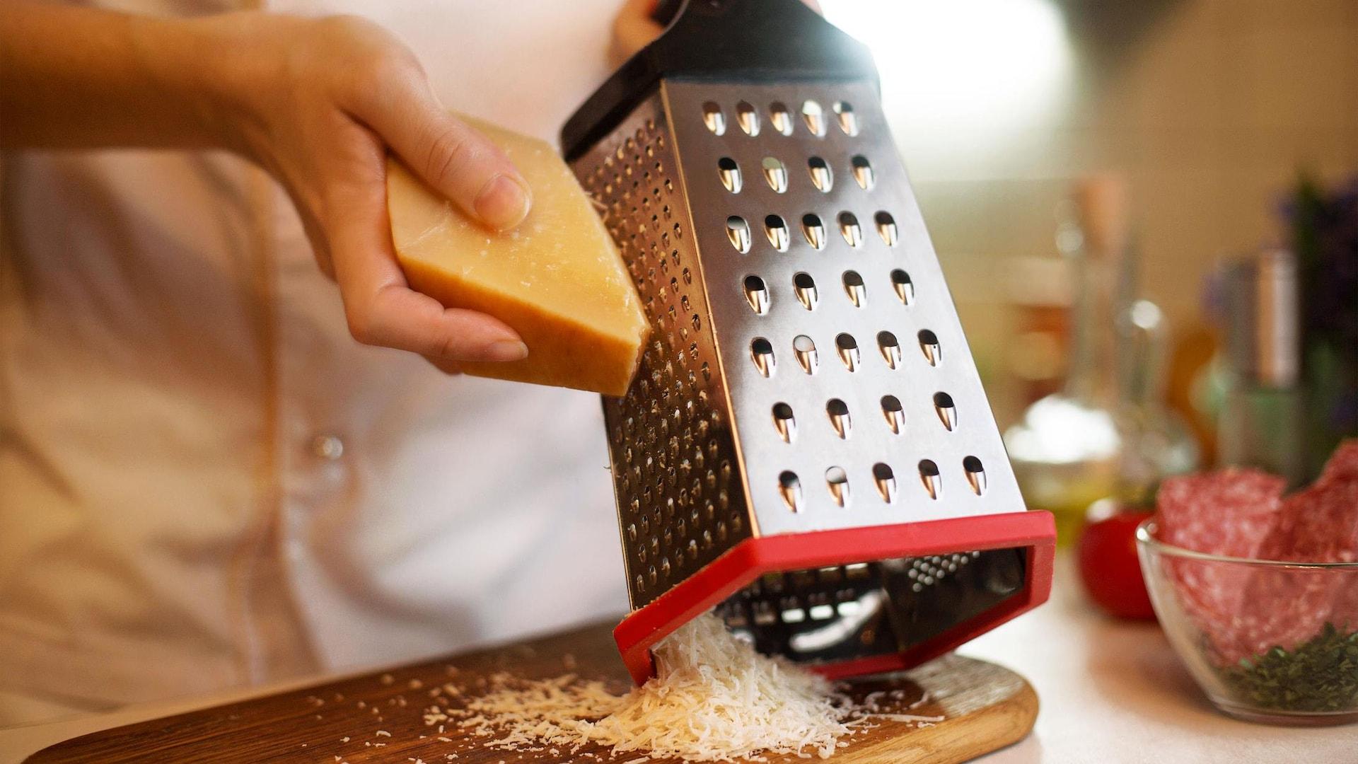 Un chef râpe un morceau de fromage.