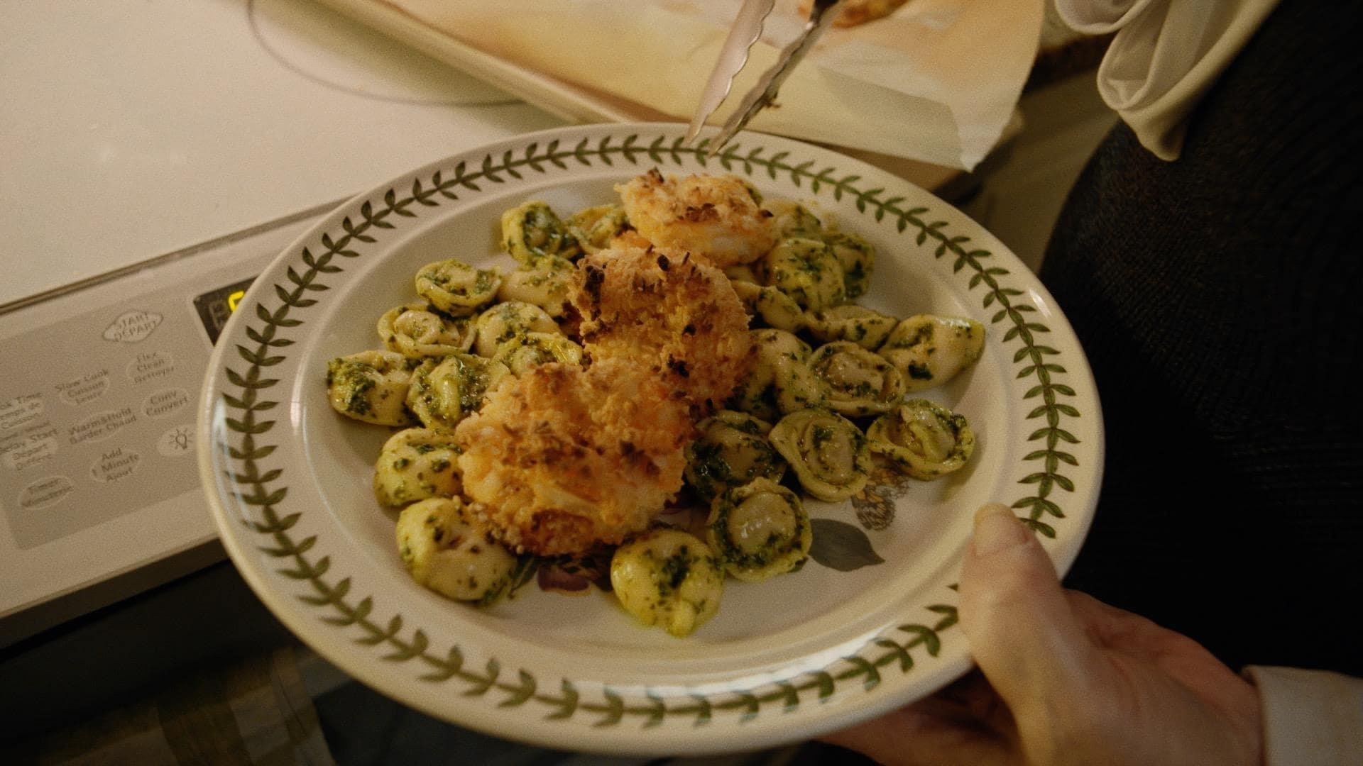 Une assiette avec crevettes croustillantes à la noix de coco et tortellinis au pesto.