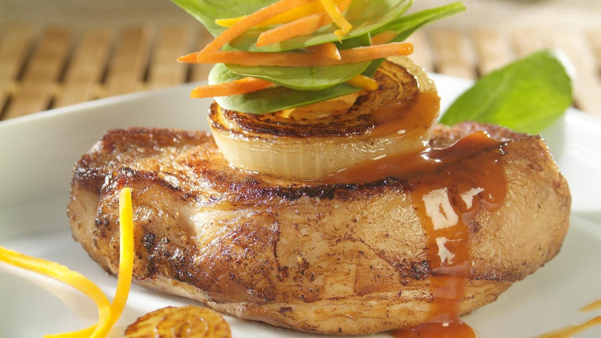 Une côte de porc avec plusieurs légumes en julienne et sauce.