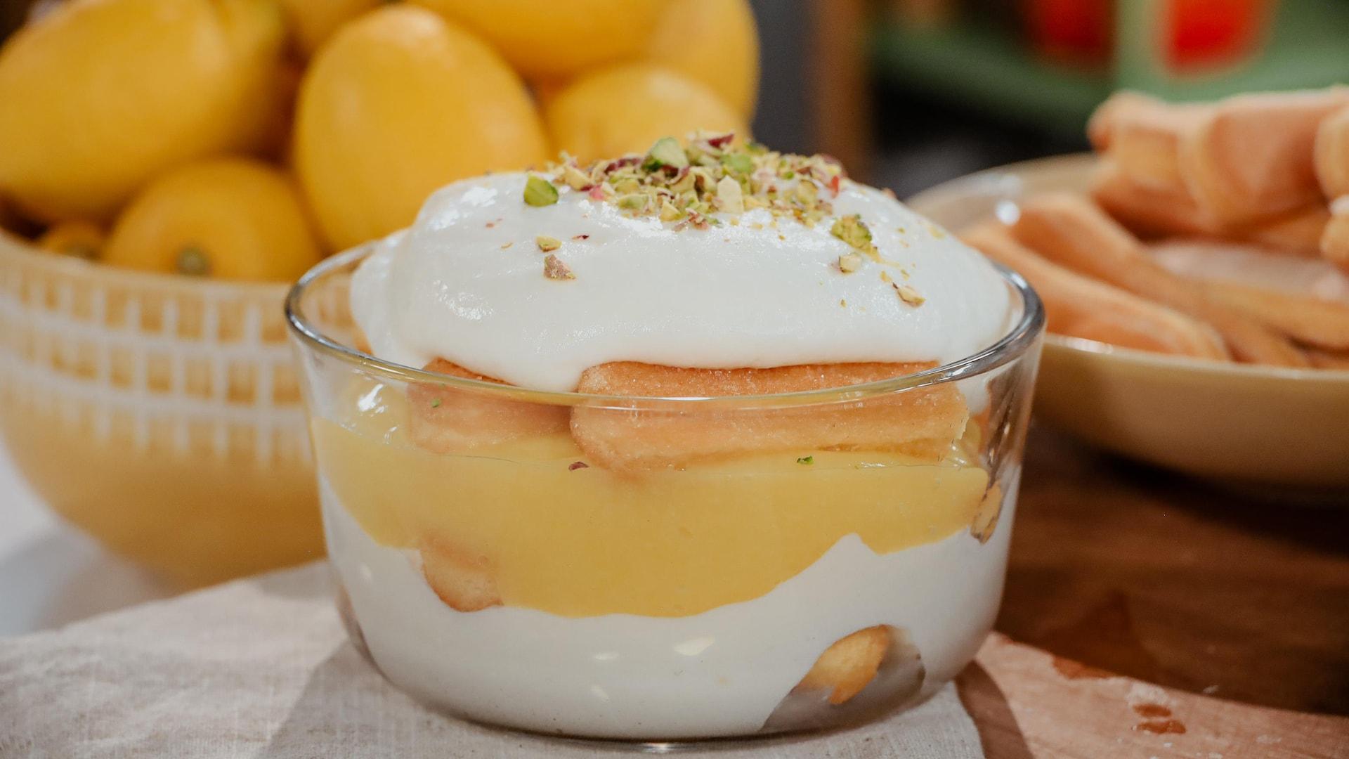 Un pouding étagé au citron, garni de crème fraiche et de pistaches hachées, servi aux côtés de citrons et de doigts de dame.
