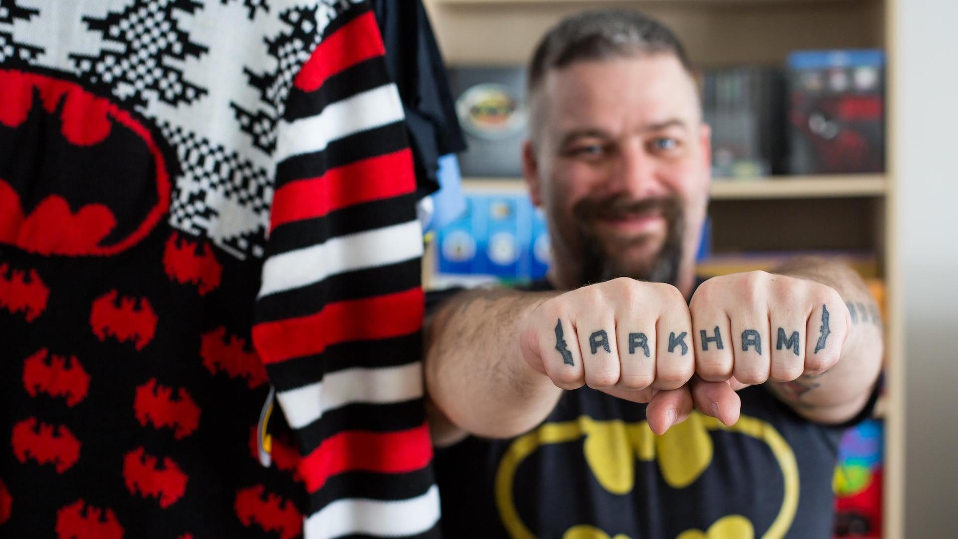 L'homme tient ses poings devant lui et chacune des lettres d'Arkham est tatouée sur un doigt différent.