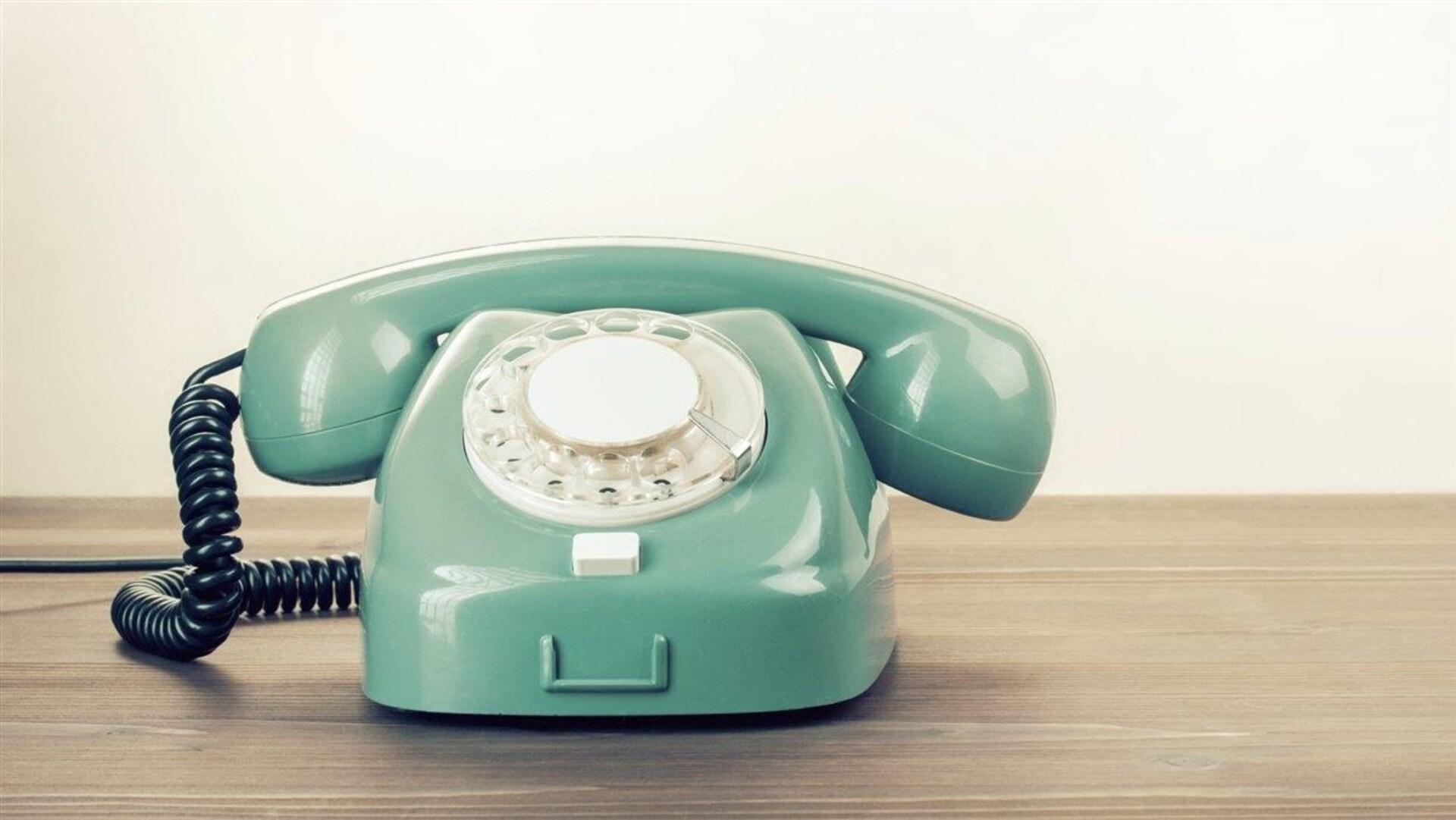 Un téléphone ancien vert posé sur une surface en bois.