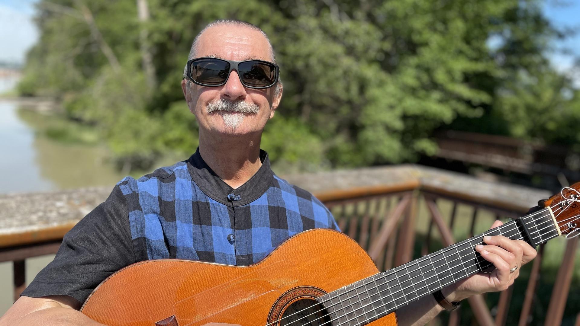 Photographie du musicien André Thibault jouant de la guitare.