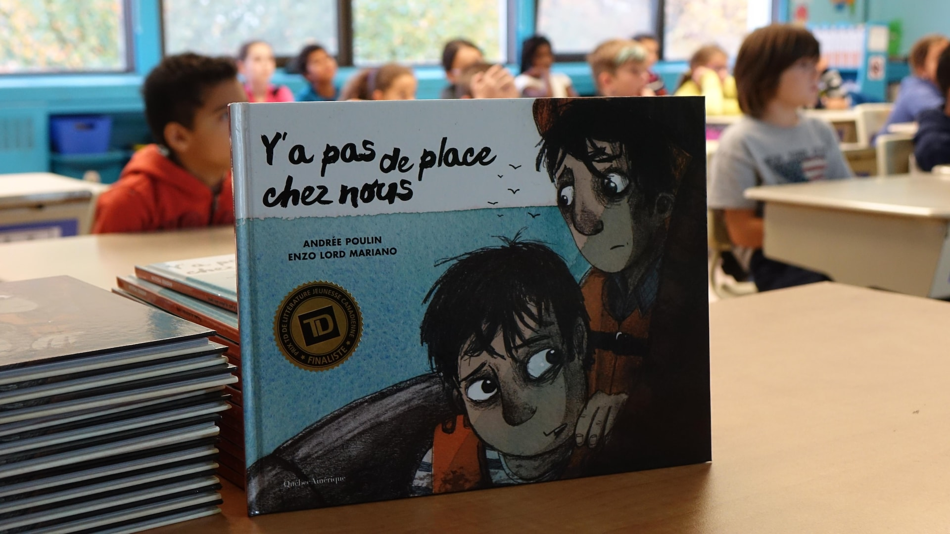 Photo du livre «Y'a pas de place chez nous» d'Andrée Poulin en avant-plan et d'une classe d'école primaire en arrière-plan.