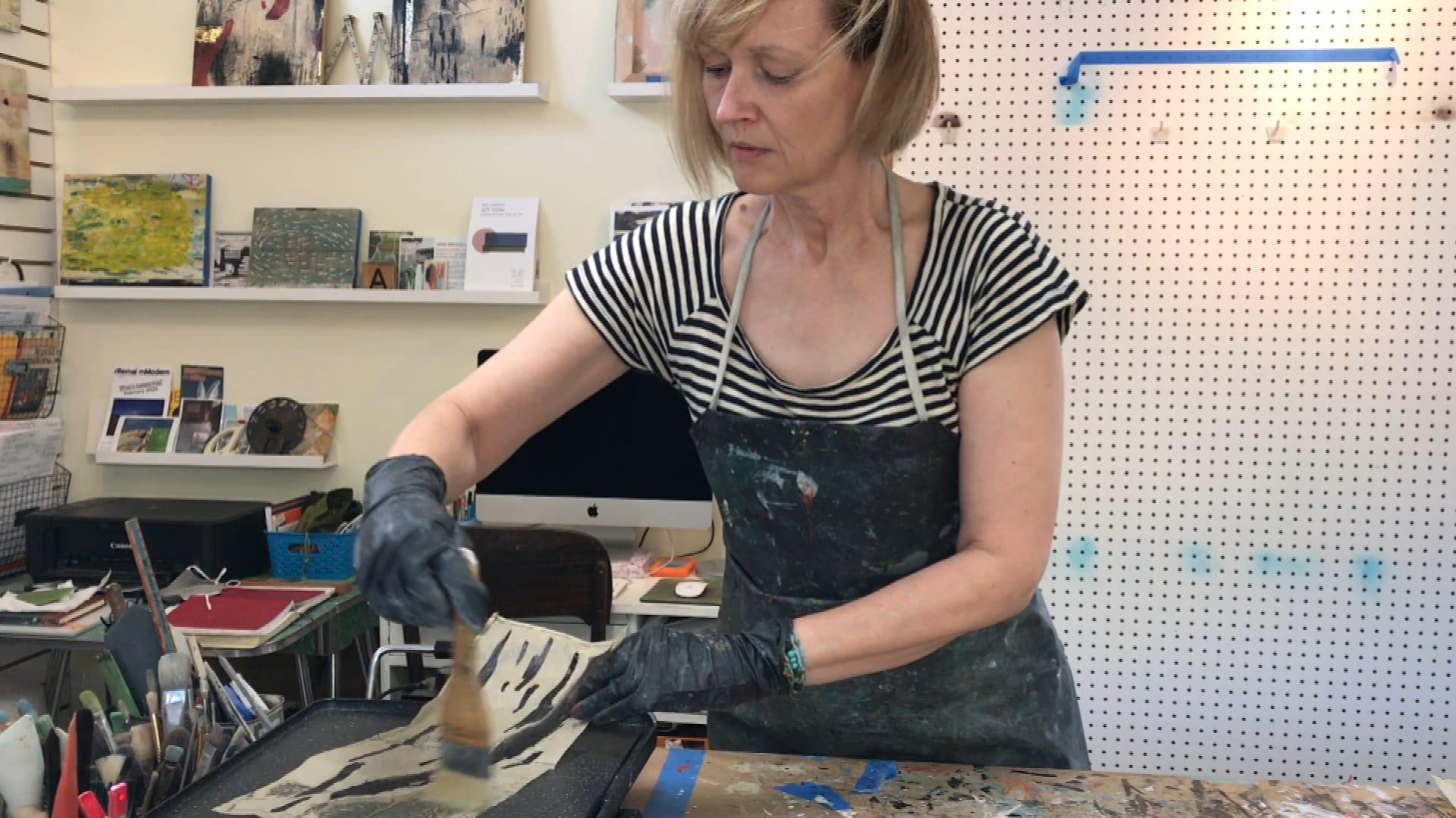 L'artiste visuelle fransaskoise Anne Brochu Lambert brosse de la peinture à cire sur du papier. Le papier est sur une plaque chauffante.