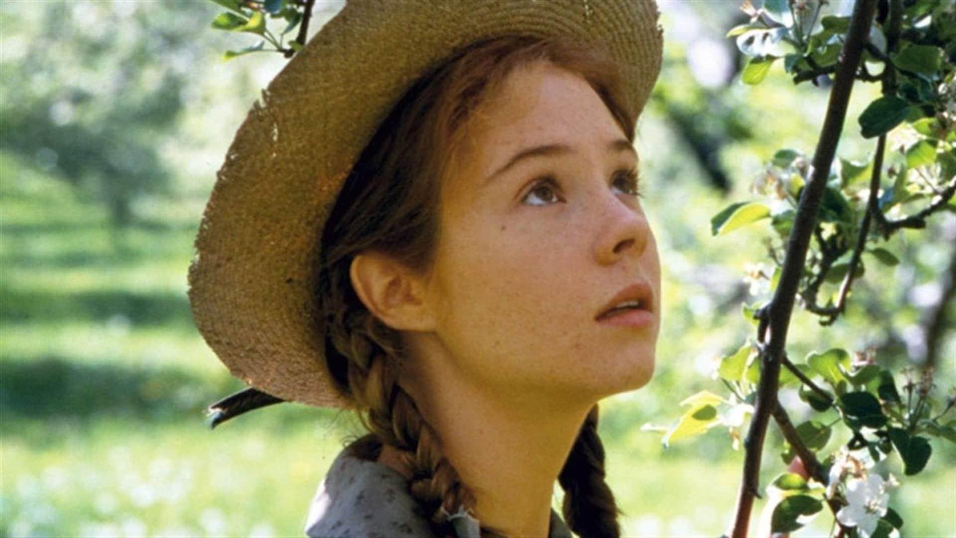 Une jeune fille rousse avec un chapeau de paille se tient près d'un arbre en fleurs.
