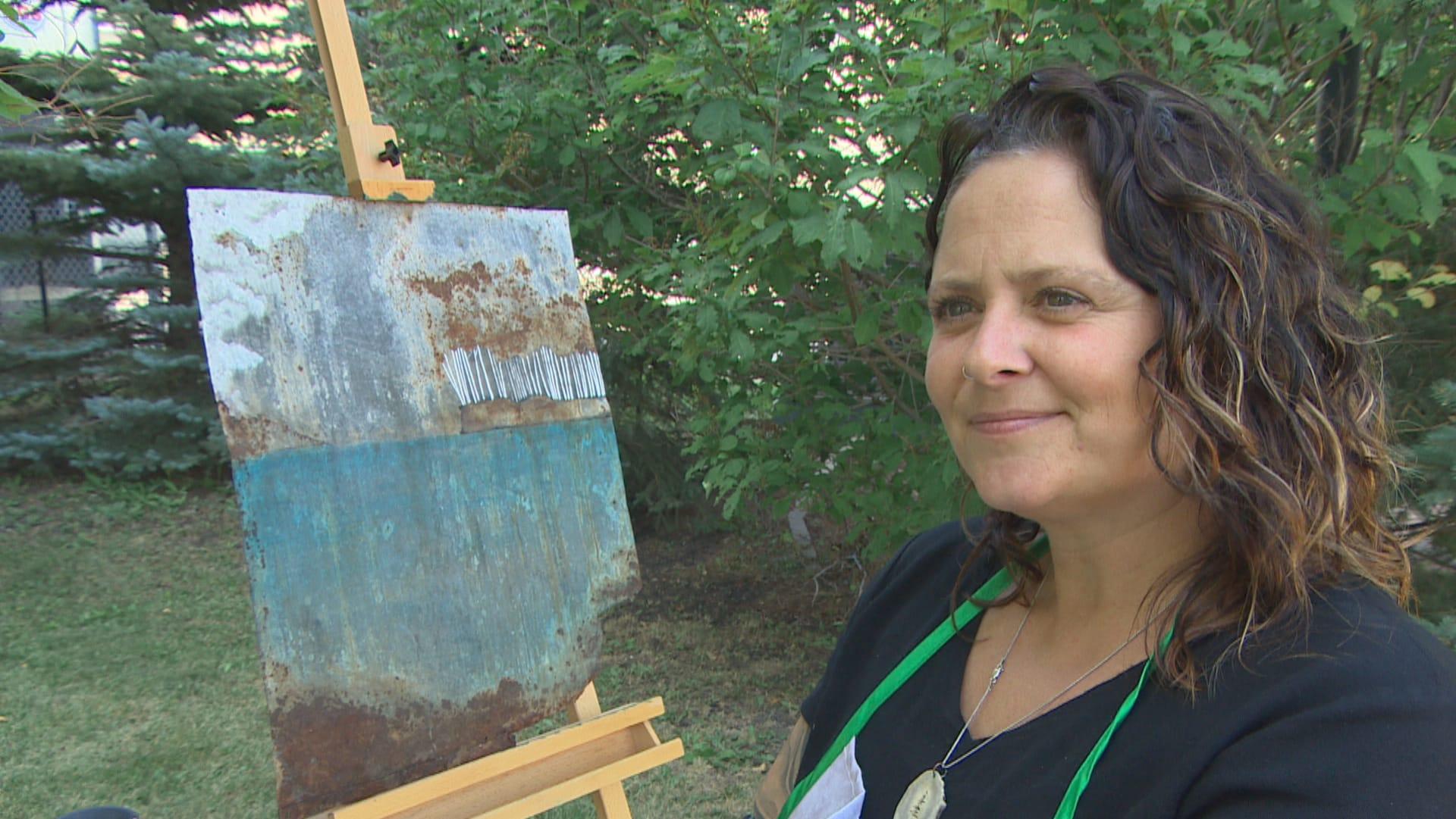 Une femme sourit. À côté d'elle se trouve une peinture sur un morceau d'étain.