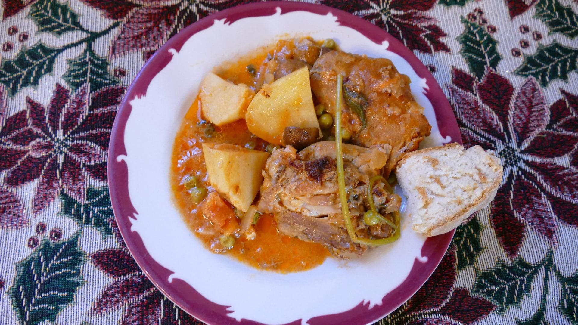 Une assiette de pommes de terre et de poulet en sauce est déposée sur une nappe avec des fleurs.