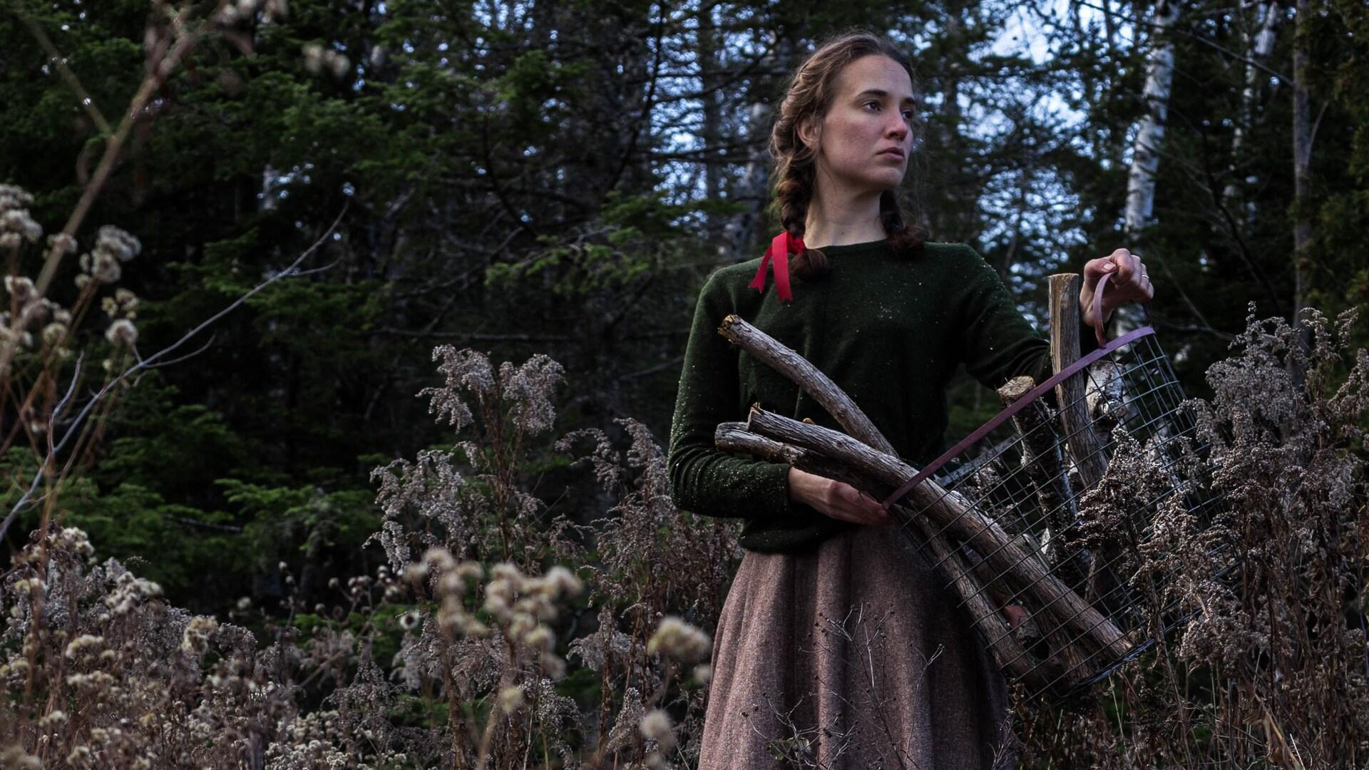 Exemple d'autoportrait narratif en couleur réalisé par Audrée Wilhelmy, écrivaine et photographe, la représentant dans la forêt tenant un panier métallique contenant du bois ramassé.