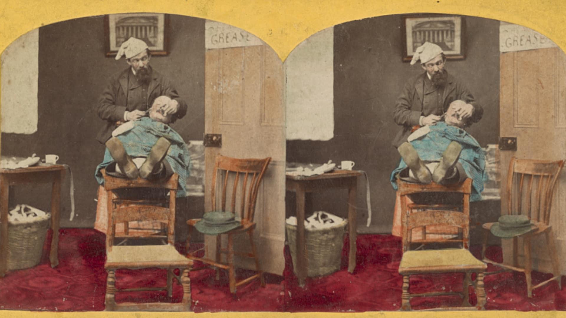 Un client se fait raser dans un salon au mobilier plutôt rudimentaire. Le client est en équilibre précaire, les deux pieds posés sur le dossier d'une chaise. Une corbeille d'osier semble déborder de linge sale sous ls table.