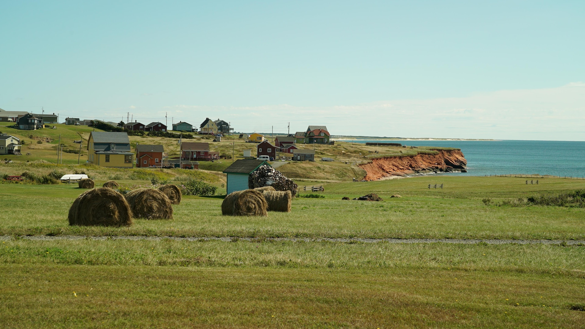 Des maisons, du foin, des falaises rouges des Îles-de-la-Madeleine.