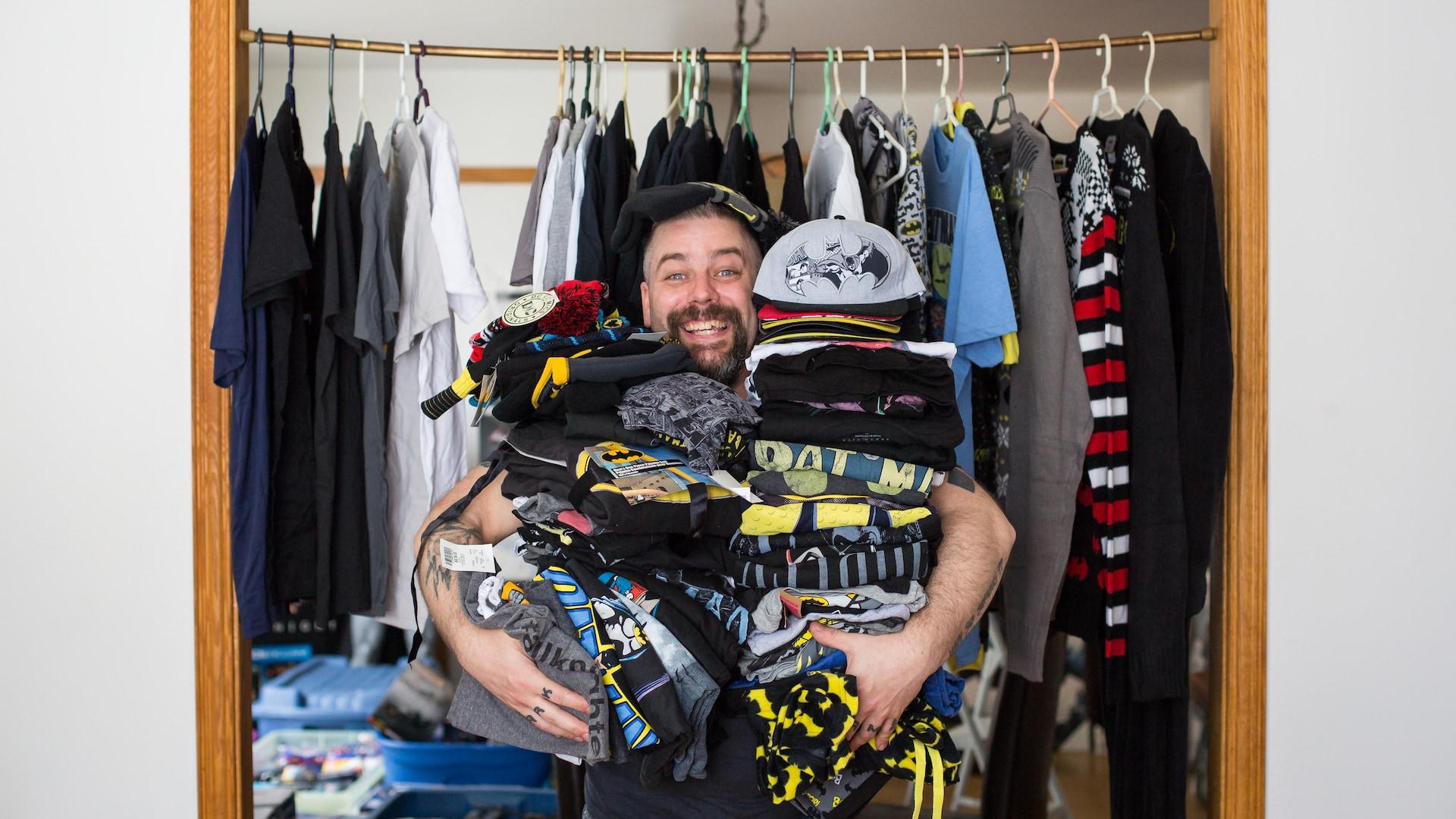 Le collectionneur sourit et tient des piles de chandails, pantalons et casquettes.