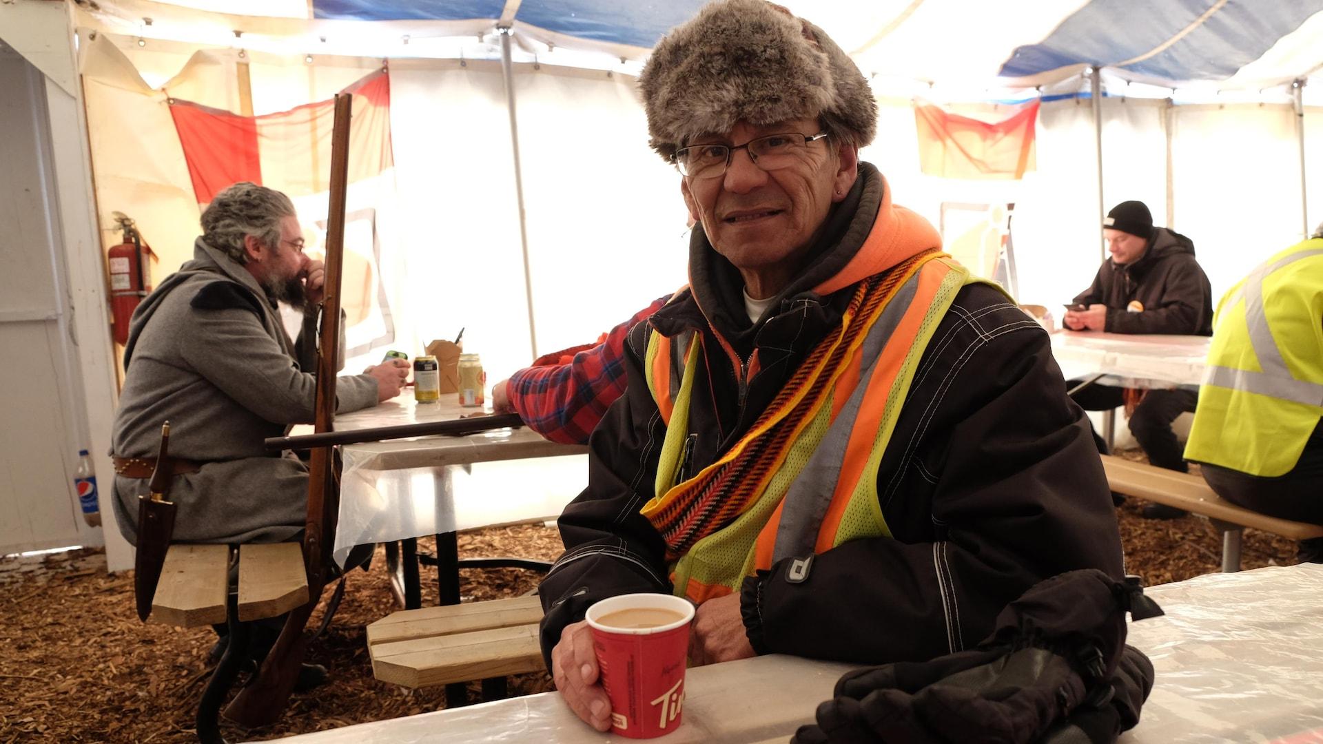 Un homme en veste de sécurité boit un café.