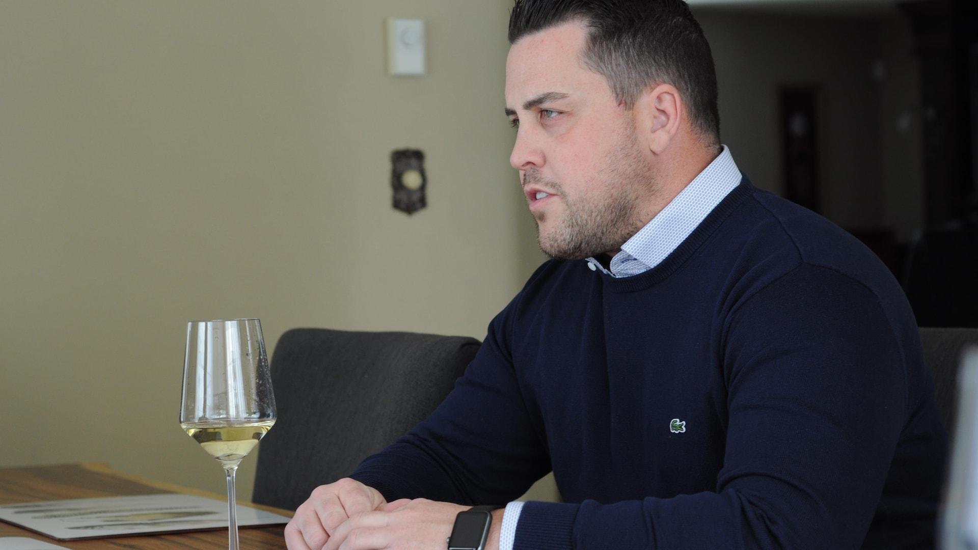 Benoît Lefebvre assis à une table de cuisine avec un verre de vin.