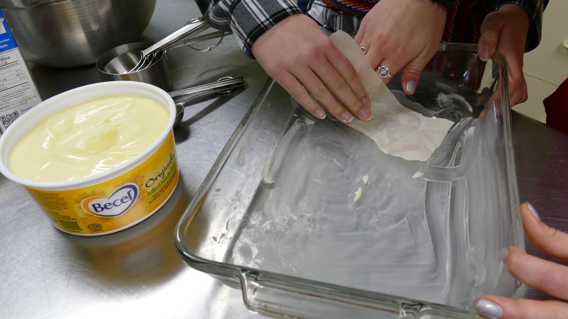 Trois mains beurrent le moule pour les brioches.