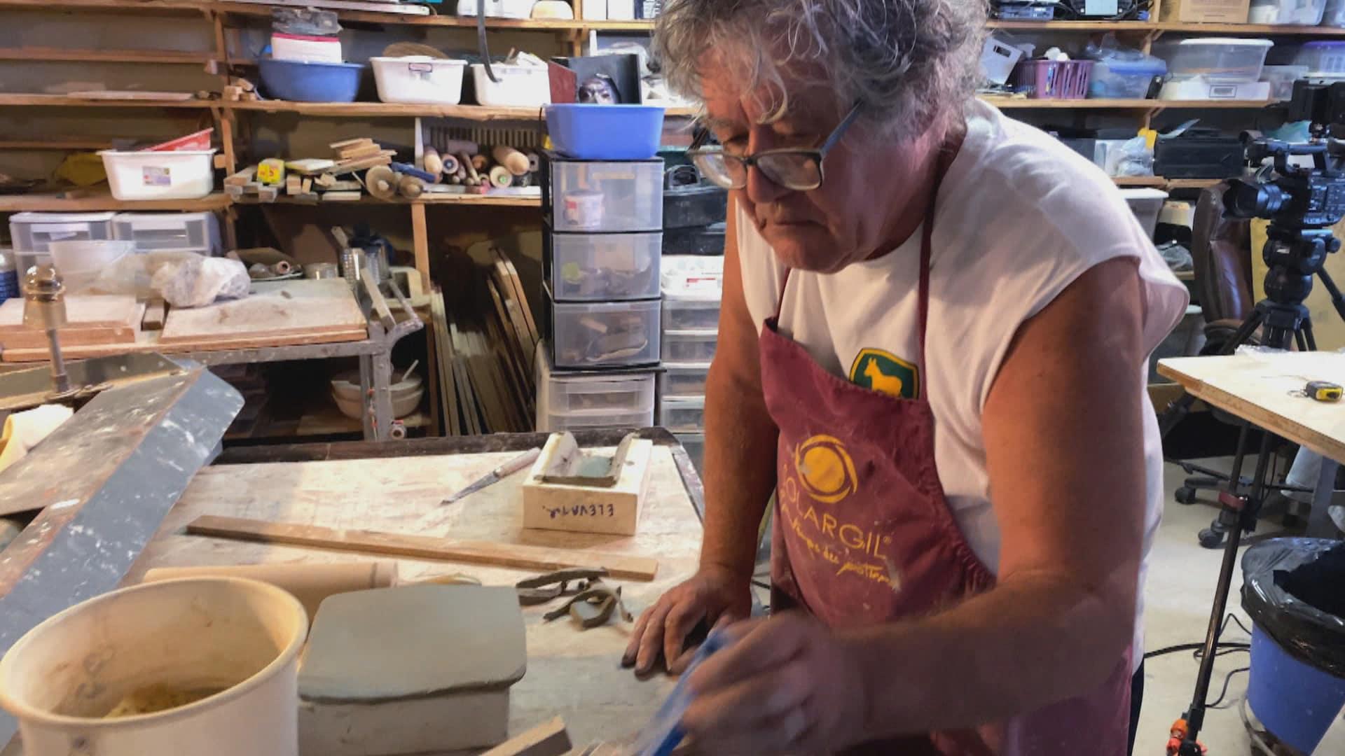 Charley Farrero prend un outil pour travailler l'argile, dans un atelier avec des étagères remplies de matériaux et d'outils.