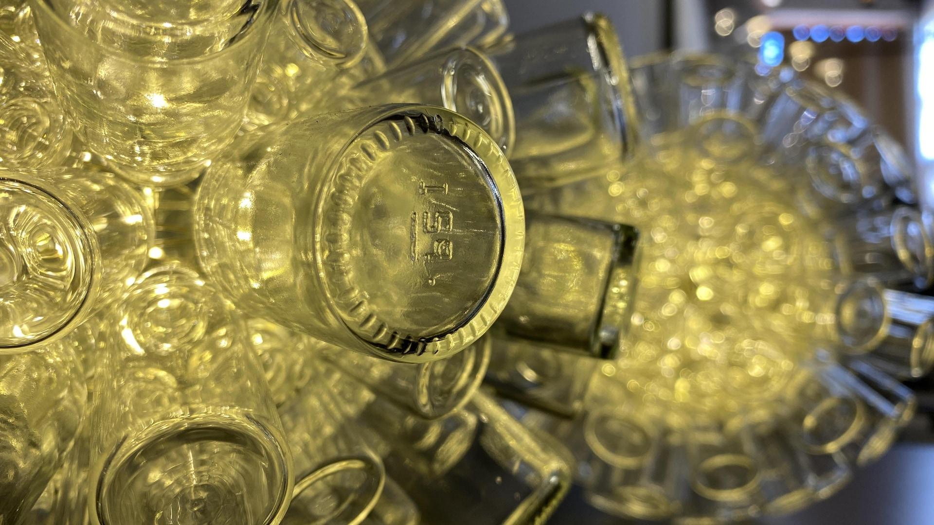 Suspension de bouteilles de verre à travers laquelle diffuse une lumière.